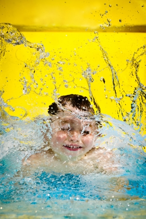 Young boy or kid has fun splashing into pool after going down water slide during summer with copy space  Stock Photo