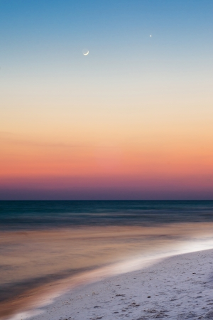 Summer beach scene just after sunset with crescent moon and venus in sky photo