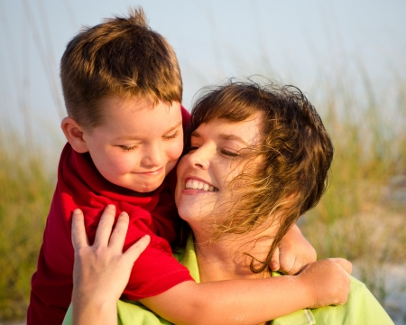 Portrait of happy mother and son hugging at beach with sand dunes in background photo