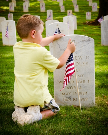MARIETTA, GA - MAY 26: Jackson Hainer, 5, of Dallas, Ga., straightens a flag on a veterans grave on May 26, 2012, for Memorial Day Weekend at the National Cemetery in Marietta, Ga.