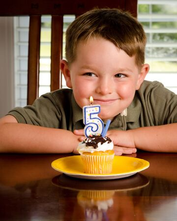 blowing out: Young boy blowing out his birthday candle Stock Photo
