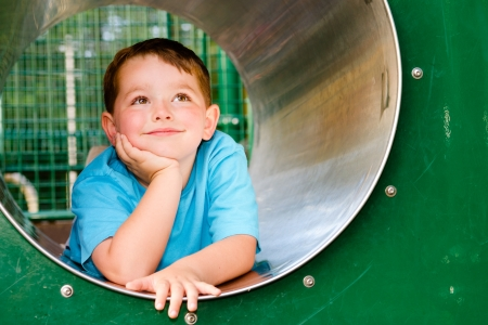 school playground: Cute young child boy or kid playing in tunnel on playground   Stock Photo