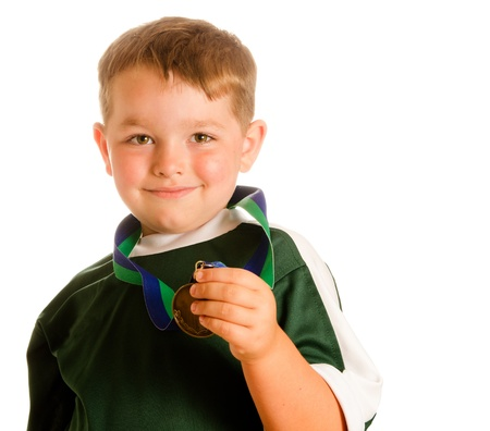 Happy child in soccer or football uniform with medal isolated on white photo