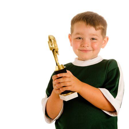 Happy child in soccer or football uniform with trophy isolated on white photo