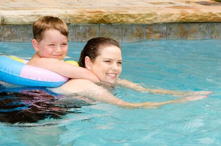 Mother and son swimming together while on vacation photo