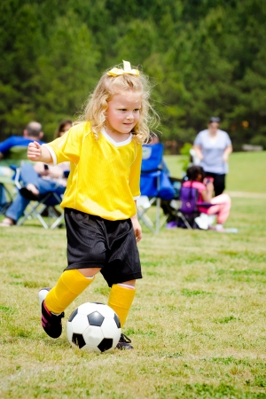 Cute young girl in uniform playing in organized youth league soccer game  photo