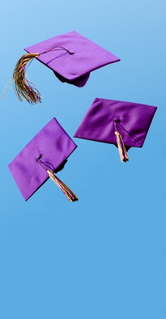Graduation caps flying in the air after being thrown with room for copy photo