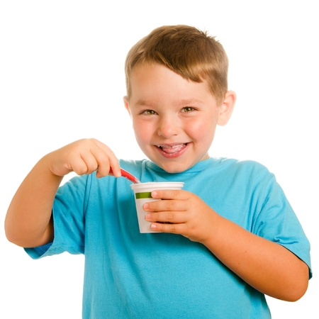 kids eating healthy: Happy smiling young child eating yogurt isolated on white