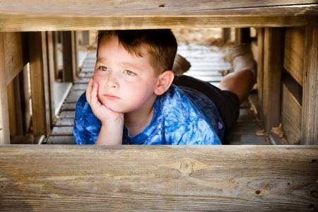 ni�os tristes: Ni�o infeliz ocultar y de mal humor mientras jugaba en el patio de