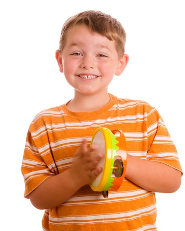Happy smiling child playing tambourine isolated on white photo