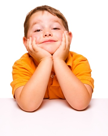 desorden: Niño travieso aburrido sentado en el escritorio