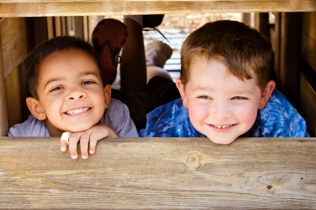 African-American child and caucasian child playing together on playground photo