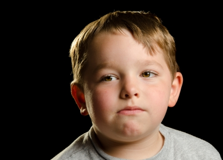 child poverty: Portrait of serious, sad, angry or depressed child isolated on black
