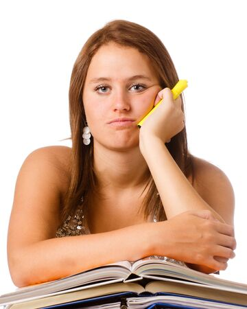 Bored unhappy teenage school girl studying with textbooks isolated on white photo