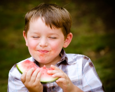 Summer portrait of cute young child eating watermelon outdoors 版權商用圖片