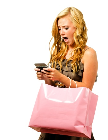 Portrait of teen girl with pink shopping bag texting with shocked or surprised expression isolated on white