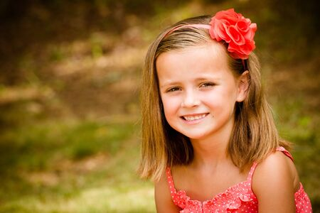 Summer child portrait of smiling pretty young girl outdoors photo