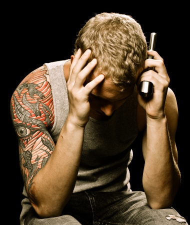 suicidal: Teen suicide depression concept with teenager male holding handgun to head  Stock Photo