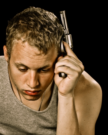 angst: Teen suicide depression concept with teenager male holding handgun to head  Stock Photo