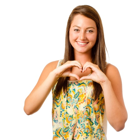 Smiling teenager girl making heart shape with her hands isolated on white