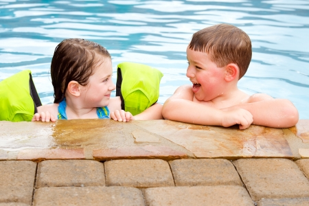 Children playing together laughing and smiling while swimming in pool photo