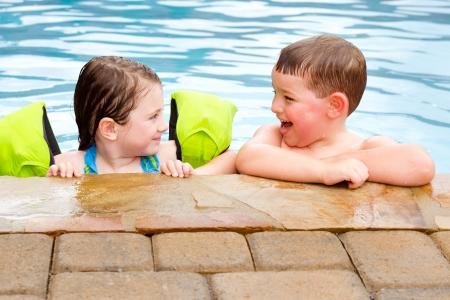 ni�os nadando: Los ni�os que juegan juntos riendo y sonriendo mientras nadaba en la piscina