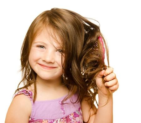 peine: Concepto de cuidado del cabello con el retrato de la niña cepillándose el pelo rebelde, largo enredado aislado en blanco