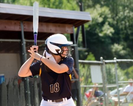softbol: Muchacha adolescente joven que juega softball en el juego organizado