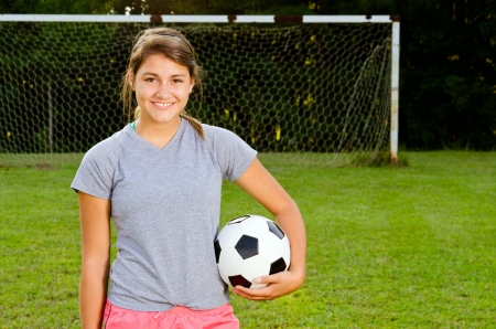 Portrait of teen girl soccer player on field photo