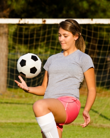 Tiener meisje jongleren voetbal bal met haar knieën