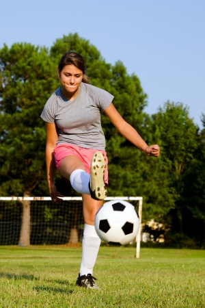 Teen girl kicking soccer ball on field Stock Photo