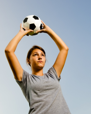 Teen girl throwing in ball while playing soccer photo