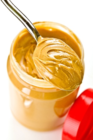 Open jar of peanut butter with spoon photo