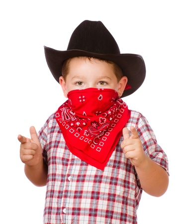 Child dressed up as cowboy playing isolated on white photo