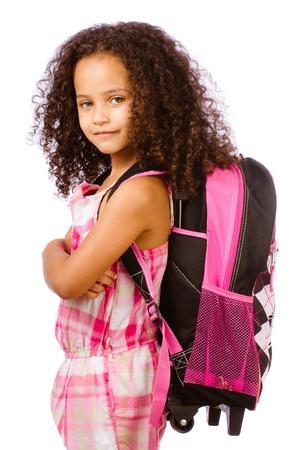 ni�o modelo: Raza mixta afroamericana mochila chica que llevaba a la escuela contra el fondo blanco Foto de archivo