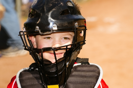 Portrait of child with catcher s equipment on during baseball game photo