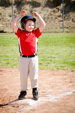 Child celebrates on base after making a hit during baseball game photo