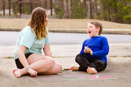babysitting: Siblings play with chalk drawing in drive way or sidewalk