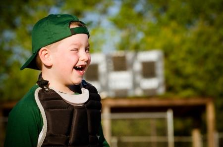 포수의 장비에서 아이의 초상화 야구를하면서 웃
