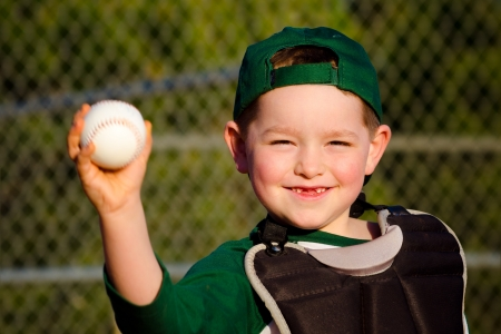 Young child in catcher s gear throwing baseball photo