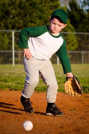 ballplayer: Young child fielding ball while playing baseball Stock Photo