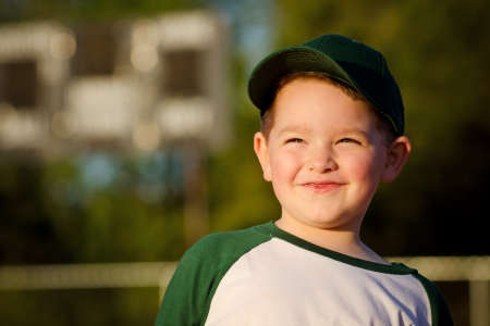 Portrait of child baseball player on field in front of scoreboard photo