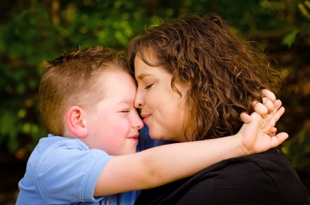 Mother and son hugging with woman kissing child photo