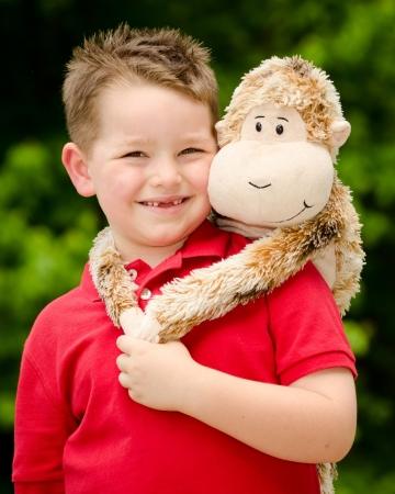 nursing bottle: Portrait of boy playing with his stuffed animal pet Stock Photo