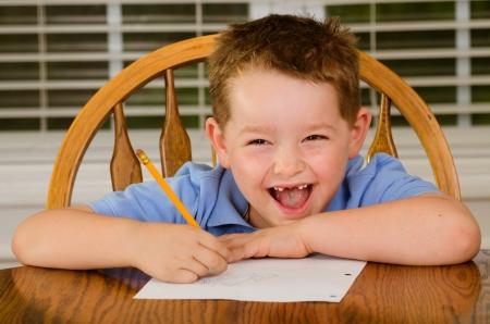 tarea escolar: Ni�o feliz haciendo su tarea en la mesa de la cocina en el hogar Foto de archivo