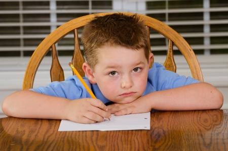 Ongelukkig kind zijn huiswerk op keukentafel thuis