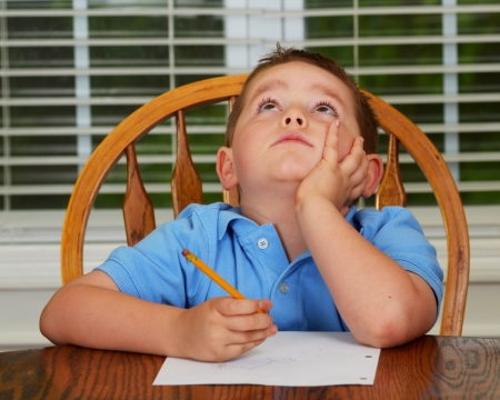 rebellious: Thoughtful child doing his homework at kitchen table at home
