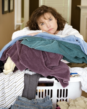 tired woman resting on large messy pile of laundry Stockfoto