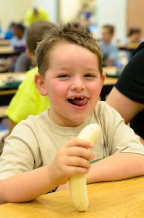 Happy child eating healthy lunch in busy school cafeteria photo