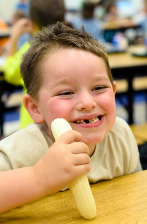 canteen: Happy child eating healthy lunch in busy school cafeteria Stock Photo